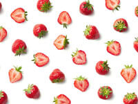 A collection of whole and chopped strawberries
