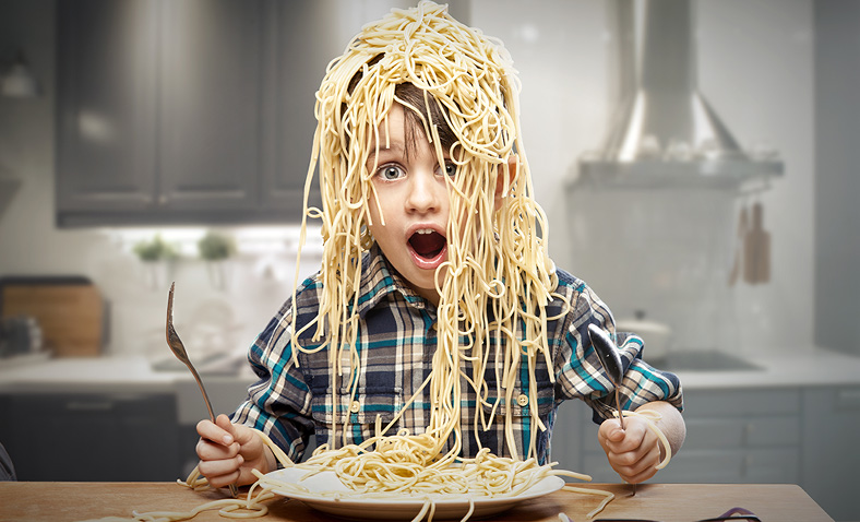 boy at table covered in spaghetti